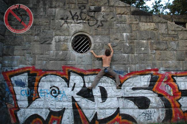 Boulderer klettert an einer Graffiti-beschmirten Wand beim Donaukanal