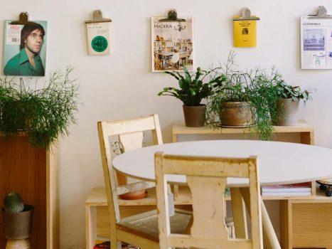 Ein kleiner Raum it Tisch, Sesseln und vielen Bildern an der Wand