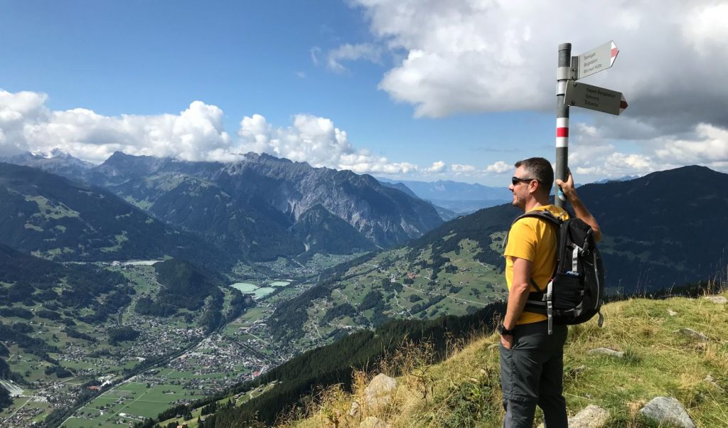 Ein Wanderer blickt vom Gipfel aus zufrieden ins Tal (Montafon, Schruns)
